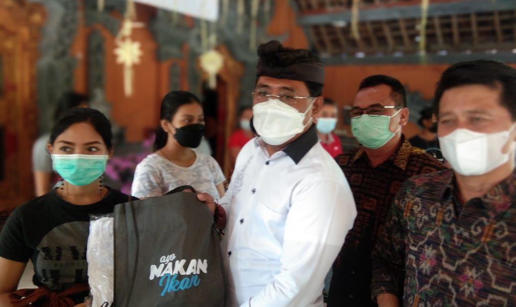 Gus Adhi Amatra saat menyerahkan Paket ikan segar didampingi Bupati Klungkung di Bale Desa Aan, Minggu (6/6)
